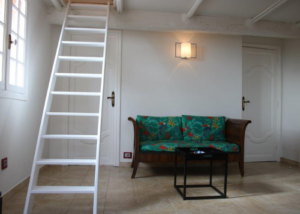 Studio's living room with an old canopee and a stairway La Romarine